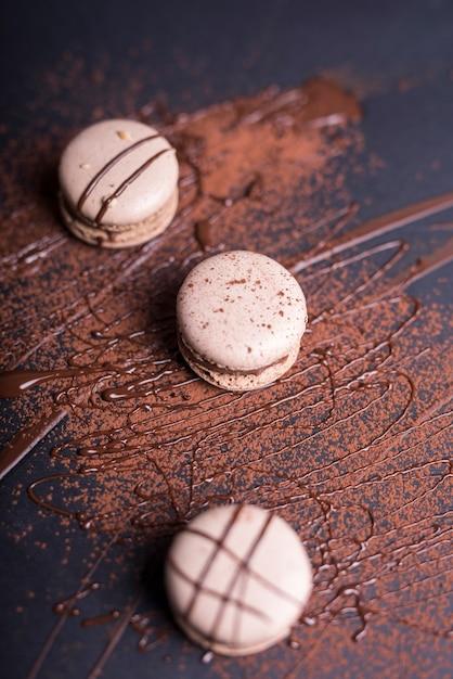 チョコレートの粉と黒の背景にマカロンの上のシロップ 無料写真