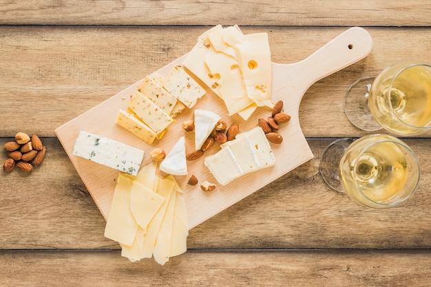 アーモンドと木製の机の上のワインとチーズの種類 無料写真