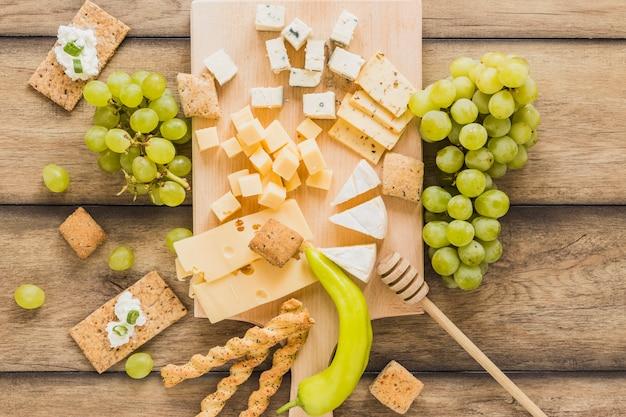 チーズブロック、ブドウ、ぱりっとしたパンとチーズクリームの俯瞰。木製のテーブルの上の緑の唐辛子 無料写真