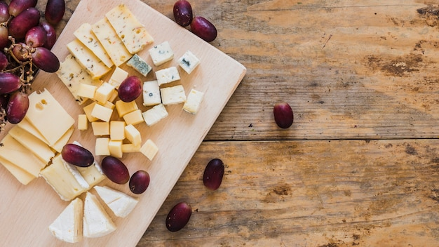 木製の机の上のブドウとチーズキューブの種類 無料写真