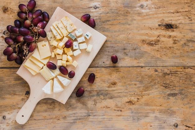 フレッシュチーズのスライスと木製のテーブルの上の赤ブドウを持つキューブの立面図 無料写真