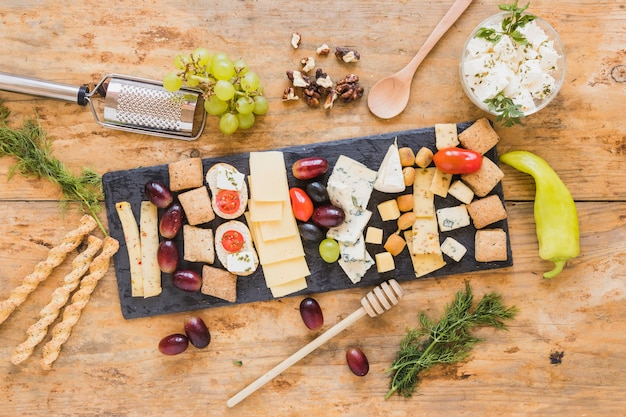 パセリ、ブドウとチーズの盛り合わせ。ハニーディッパー。ブレッドスティックと木の表面にピーマン 無料写真