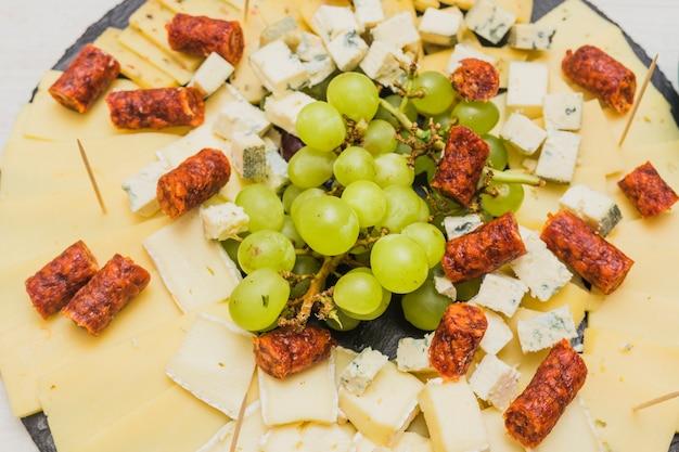 ブラックスレート板にチーズの盛り合わせとスモークソーセージとブドウの房 無料写真