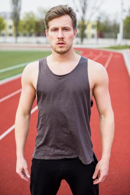 陸上競技場に立っているフィットネスの若い男の肖像 無料写真