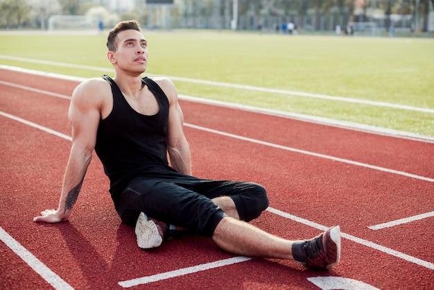 リラックスした陸上競技場に座っている筋肉の若い男性アスリート 無料写真