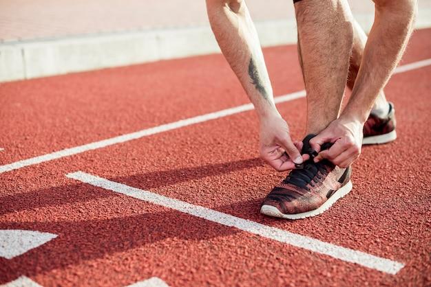 Низкая часть спортсмена мужского пола на линии старта, связывающей его шнурок на беговой дорожке Бесплатные Фотографии