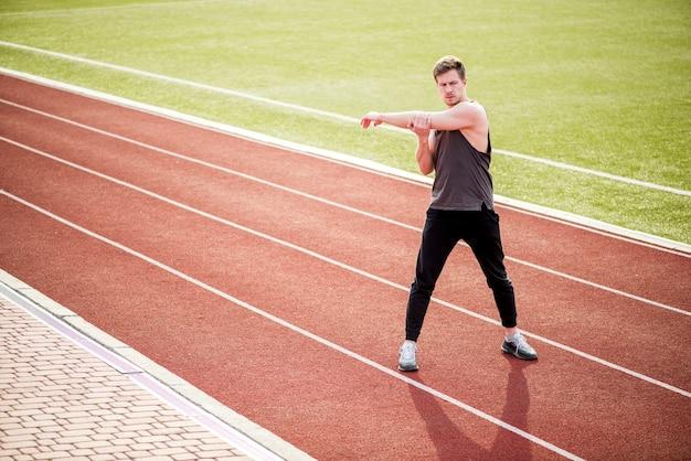 Молодой человек стоял на красной гоночной трассе, протягивая руку Бесплатные Фотографии