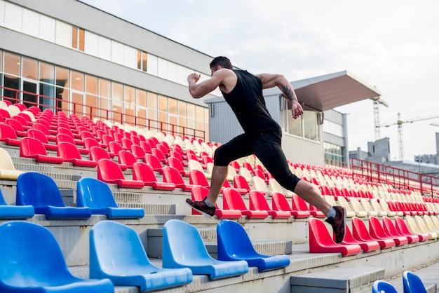 スタジアムの椅子の階段を走っている男のクローズアップ 無料写真