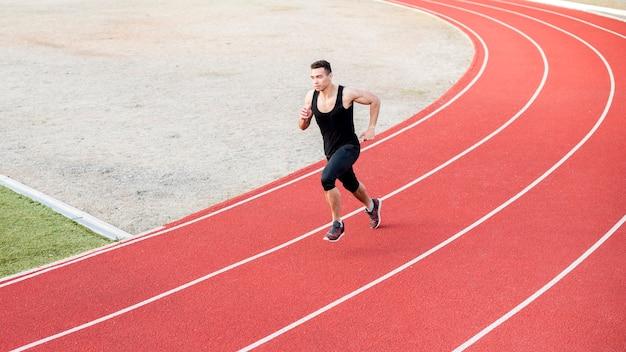 陸上競技場で実行されている男性フィットネス運動男 無料写真