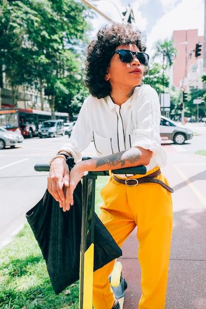 電動スクーターが付いている都市の現代の女性 無料写真