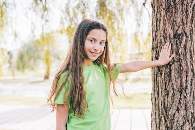 木の幹に彼の手に触れる女の子の肖像画を笑顔 無料写真