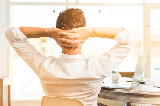 頭の上の彼の手で椅子に座っている実業家の背面図 無料写真