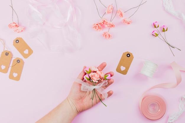 Крупный план женской руки, держащей цветок, перевязанный белой лентой на розовом фоне Бесплатные Фотографии