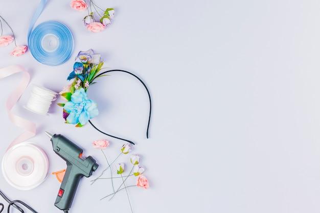 Вид сверху сине-белой ленты; искусственный цветок; клеевой пистолет для создания ленты на белом фоне Бесплатные Фотографии