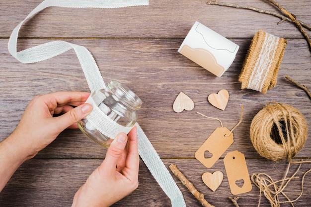 Крупный план руки женщины, наклеивающей белую кружевную ленту на стеклянную бутылку над деревянным столом Бесплатные Фотографии