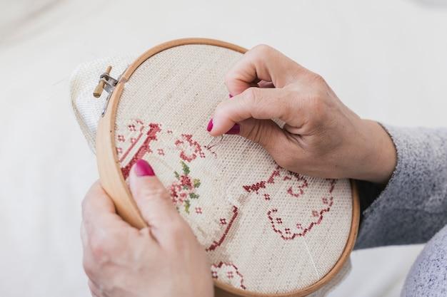 針でクロスステッチフープに刺繍をする女性の俯瞰 無料写真