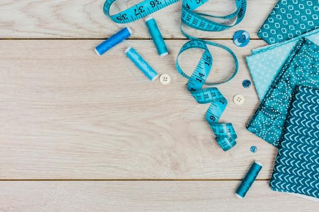 測定テープの俯瞰図。スレッドスプールボタンと木製のテーブルの上の折り畳まれた服 無料写真
