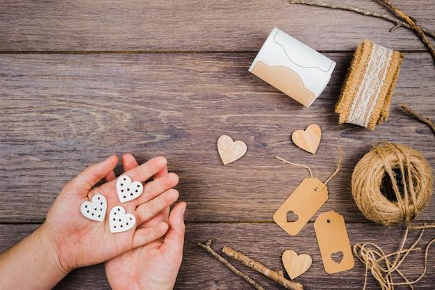 Рука человека, держащая сердечко с джутовой шпулей; теги; палочки и кружева на деревянный стол Бесплатные Фотографии