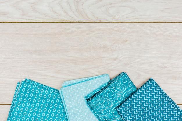 木製の机の上の異なるプリントと折られた青い服の高架ビュー 無料写真
