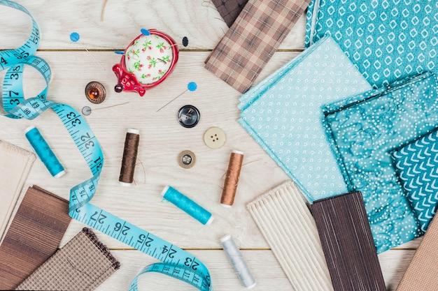 Кнопки; набор игл; катушки с нитками необходимы для шитья одежды на деревянном столе Бесплатные Фотографии