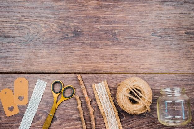 Ключевые слова; ленты; ножницеобразный; палочки; джутовая шпуля и пустая прозрачная банка на деревянном столе Бесплатные Фотографии