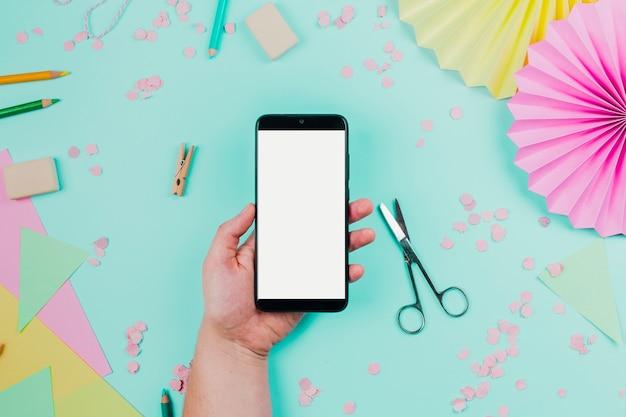 ティールを背景に白い画面表示と携帯電話を持っている人の手のクローズアップ 無料写真