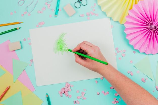 ティールの背景の上の白い紙の上の緑の鉛筆で描く人の俯瞰 無料写真