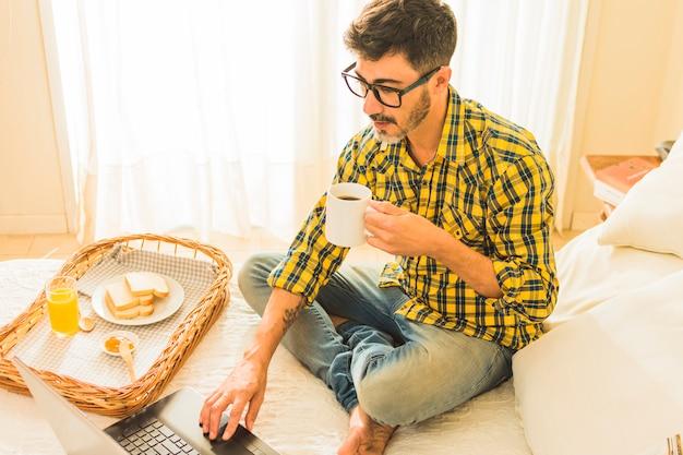 Вид сверху человека, сидящего на кровати, держа чашку кофе, используя ноутбук Бесплатные Фотографии
