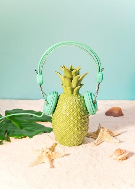 Пластиковый ананас в наушниках на пляже Бесплатные Фотографии