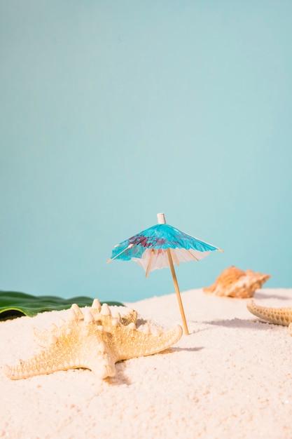 カクテルの傘とビーチのヒトデ 無料写真