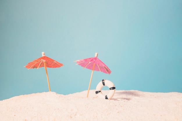 赤いパラソルと救命浮輪のビーチ 無料写真