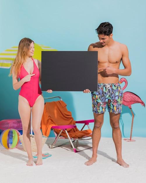 ビーチで暗い空白カードを保持している若いカップル 無料写真