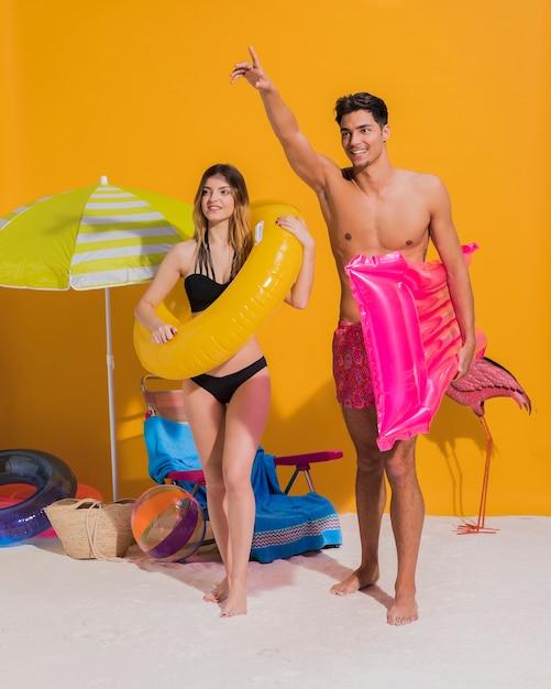 Счастливая молодая пара с плавательный круг и матрас на пляже Бесплатные Фотографии