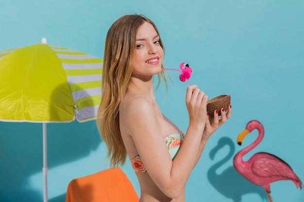 スタジオでトロピカルカクテルを持って笑顔の若い女性 無料写真