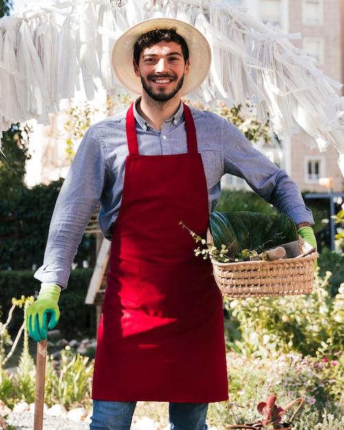 バスケットとツールを保持しているエプロンで笑顔の若い男性庭師 無料写真