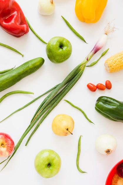 Свежий зеленый лук; томаты; огурец; яблоко; груши; лук; сладкий перец и зеленая фасоль на белом фоне Бесплатные Фотографии