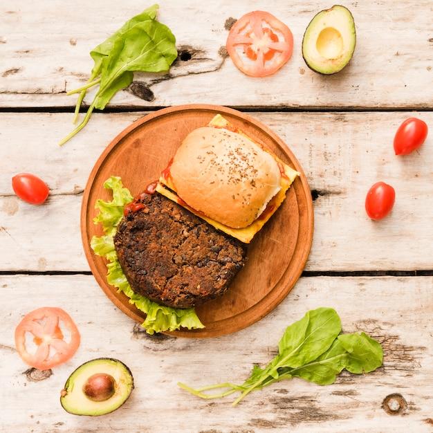 テーブルの上の円形の木の板にレタスとチーズのハンバーガー 無料写真
