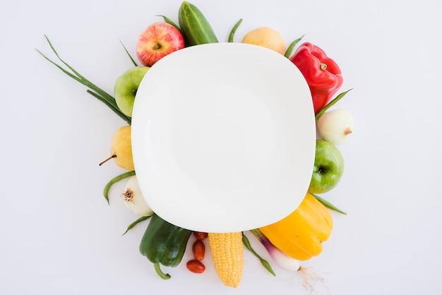 きゅうりの上の白い皿。林檎;ピーマン;玉ねぎ;トウモロコシと白い背景の上のネギ 無料写真