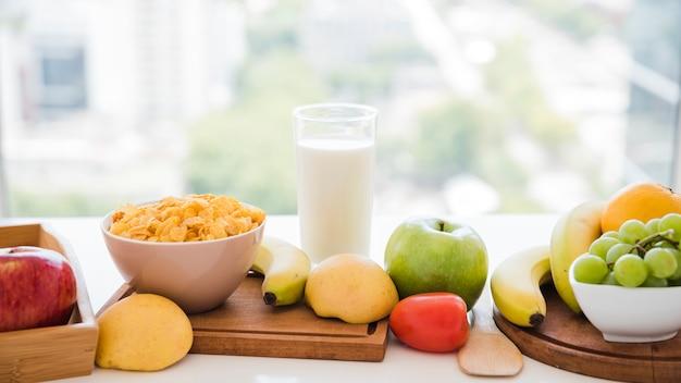 コーンフレーク;フルーツ窓の近くのテーブルの上のミルクガラス 無料写真