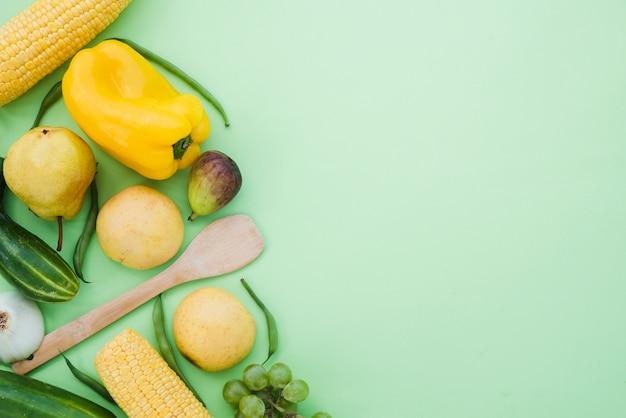 コーン;黄ピーマン。きゅうり;洋ナシ;イチジク;ぶどうとミントグリーンの背景に豆 無料写真