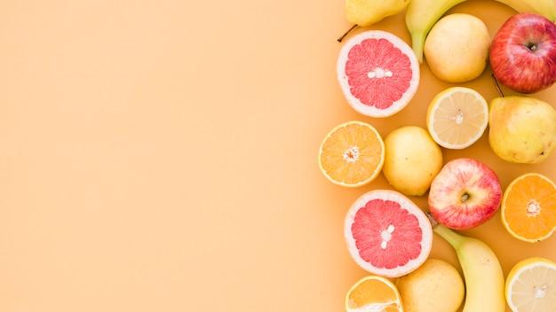Поперечные сечения лимонов; оранжевый; яблоко; груши и бананы на бежевом фоне Бесплатные Фотографии