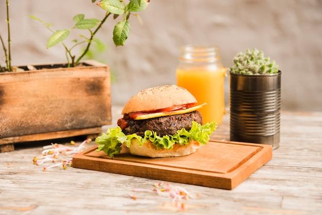 Гамбургер с салатом и сыром на разделочную деревянную доску с бутылкой сока на столе Бесплатные Фотографии