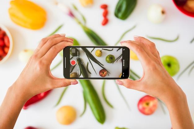白い背景の上の野菜の写真を撮る人のクローズアップ 無料写真
