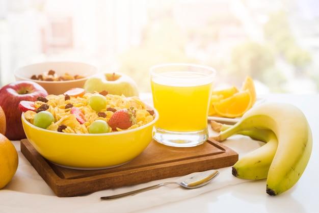 Кукурузные хлопья с фруктами; стакан сока на разделочную доску над столом Бесплатные Фотографии