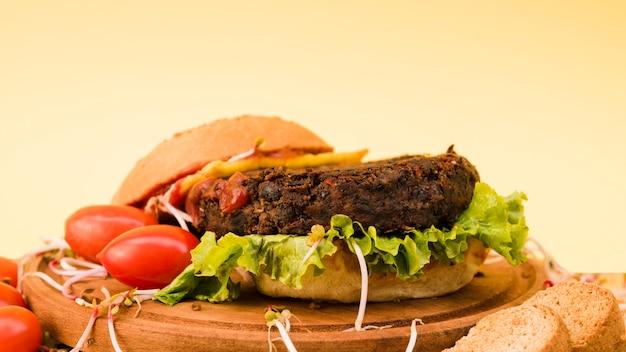 黄色の背景上のまな板にレタスとトマトのハンバーグのクローズアップ 無料写真