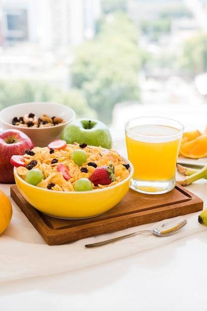 コーンフレークで健康的な朝食。ドライフルーツ;テーブルの上のリンゴとジュースのガラス 無料写真