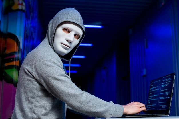 マスクを持つハッカーの肖像画 無料写真