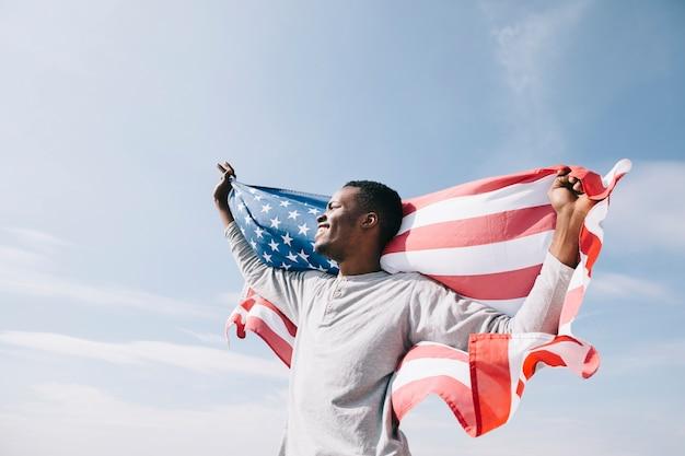 自由を象徴するアメリカの国旗と黒人男性 無料写真