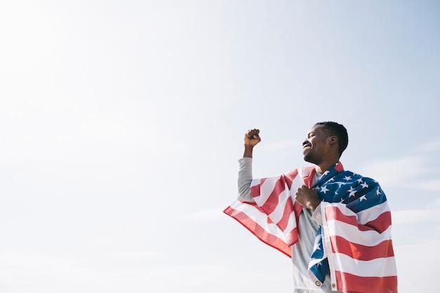 アメリカの国旗に包まれたアフリカ系アメリカ人の男 無料写真