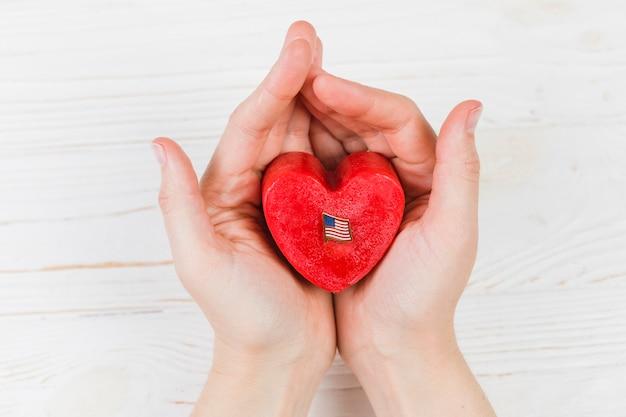 Маленькая подарочная коробка в форме сердца в руках Бесплатные Фотографии